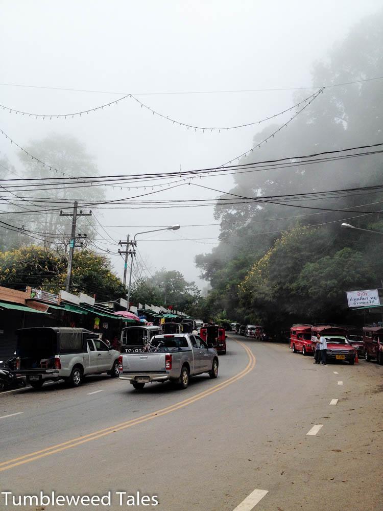Oben an der Straße: Songthaews karren die Touristen nach oben. Der Nebel verdichtet sich