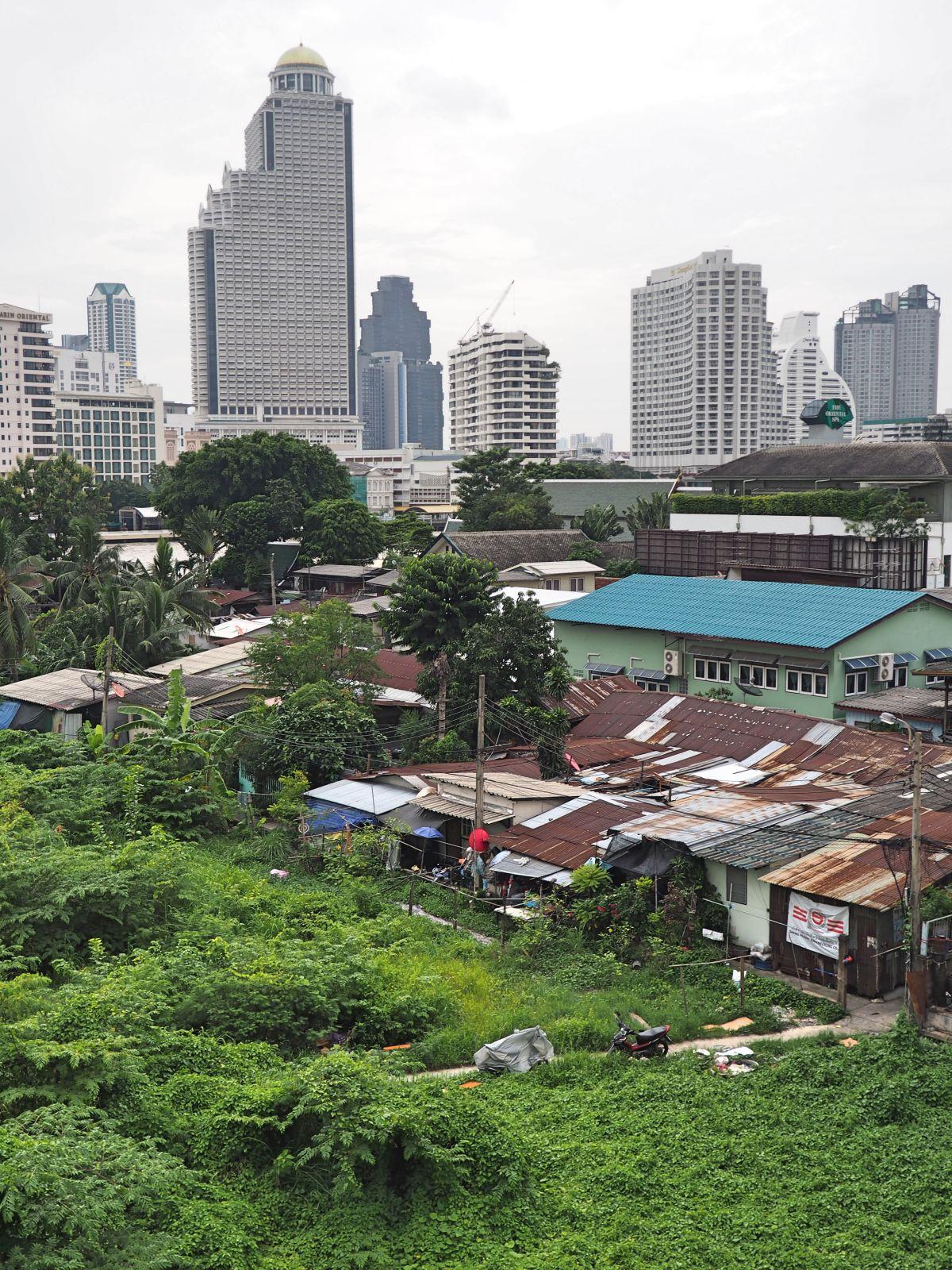 Wellblechhütten am Flussufer; dahinter auf der anderen Flussseite eines der protzigsten Gebäude in Bangkok